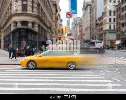 Motion blur of yellow taxi cab speeding through an intersection on 23rd Street in Midtown Manhattan New York City NYC - Stock Photo
