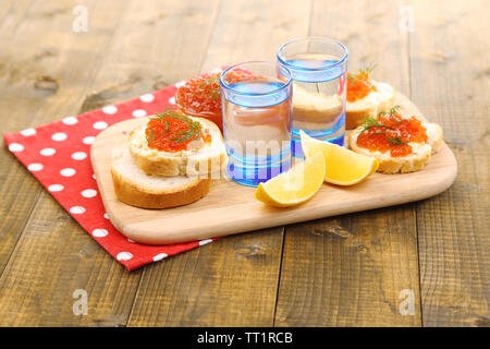Red caviar in bowl and vodka on wooden board , on napkin on wooden background - Stock Photo
