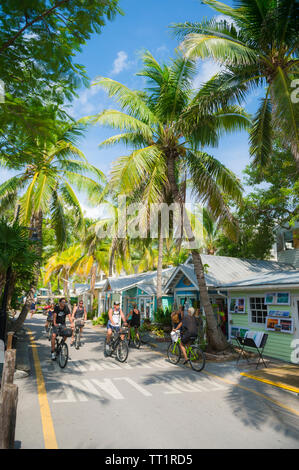 KEY WEST, FLORIDA, USA - SEPTEMBER, 2018: Visitors ride bicycles along an street lined with brightly colored cottages converted to shops in Old Town. - Stock Photo