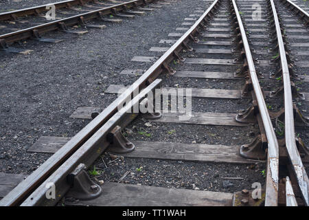 Perspective view of lines of hot rolled steel railway tracks, links, fasteners, sleepers and ballast at Didcot Railway Centre, Oxfordshire, UK. - Stock Photo