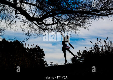 A jumping girl silhouette under the tree