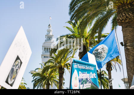 Signs waving in front of the San Francisco Ferry Building and palm trees at the Rise for Climate March, part of Global Climate Action Summit 2018 - Stock Photo