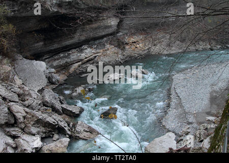 A stormy mountain river flows among the cliffs in the Khadzhokhskaya gorge. - Stock Photo