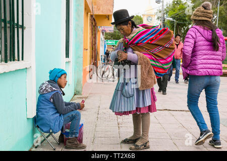 Uyuni, Bolivia - Dec 31, 2018:   Woman in traditional costume on the market in main street of Uyuni,  Bolivia. - Stock Photo