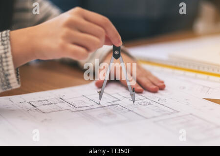 An architect using compass to draw and measure shop drawing in office - Stock Photo