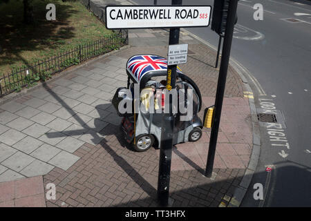 A disabled person drives her mobility scooter on the pavement on the Camberwell Road in Southwark, on 11th June 2019, in south London, England. - Stock Photo