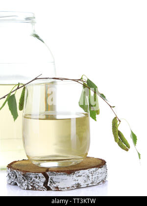 Glass and large flagon of fresh birch sap isolated on white - Stock Photo