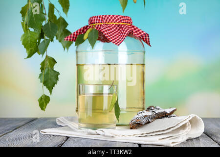 Glass and large flagon of fresh birch sap  on a wooden table on nature background - Stock Photo