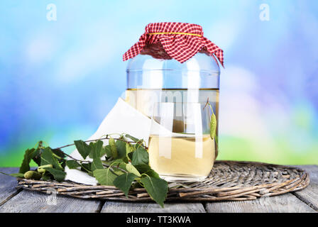 Flagon of birch juice on wicker round mat on wooden table on nature background - Stock Photo