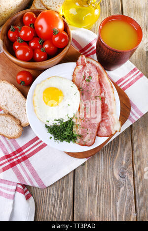 Scrambled eggs with bacon and vegetables served on plate on napkin - Stock Photo