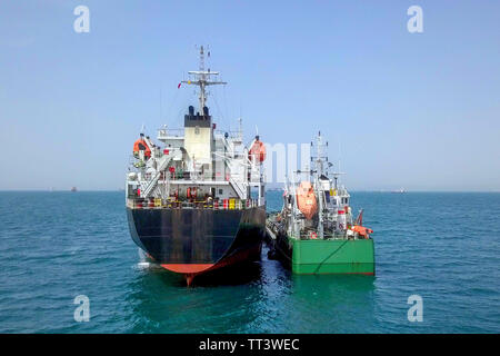 Refuelling at sea - Small Oil products ship fuelling a large Bulk carrier, aerial image. - Stock Photo