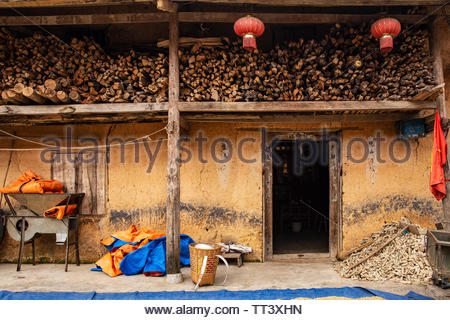Traditional hmong house in Ha Giang Province, Northern Vietnam, with chinese red lanterns, Vietnamese flag and farming stuff. - Stock Photo