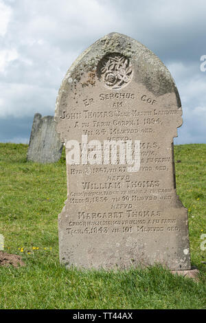 Headstones in the graveyard of The Church of the Holy Cross (Welsh: Eglwys y Grog) at Mwnt Bay, Ceredigion, Wales - Stock Photo