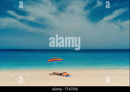 Carefree elderly man sun tanning on sandy beach in shade of striped umbrella with beautiful sea view - Stock Photo