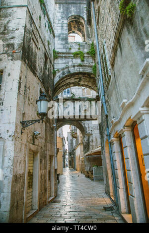 Stone houses with windows and balconies in narrow street of old town of Split, Croatia, inside the palace of Roman emperor Diocletian - Stock Photo