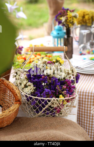 Basket with flowers on table, outdoors - Stock Photo