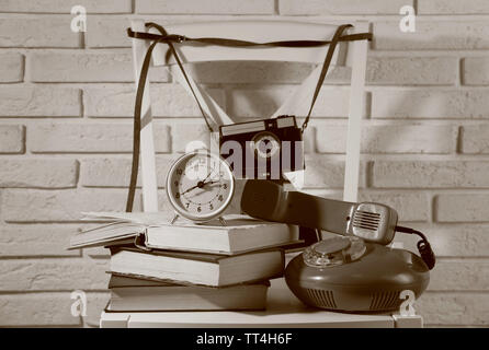 Old retro camera in composition with another retro things on wall background - Stock Photo
