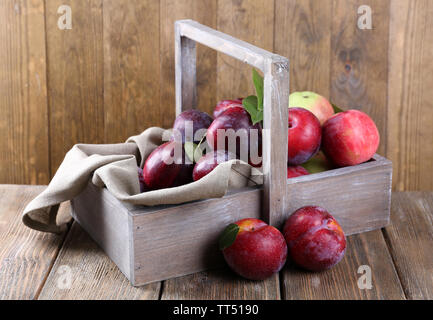 Sweet plums in wooden basket on table on brown background - Stock Photo