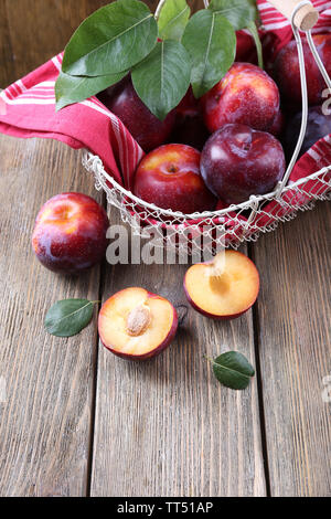 Sweet plums in wicker basket on wooden background - Stock Photo
