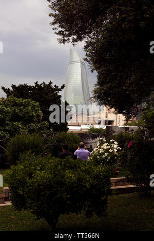 Two tourists take photos of one of the Flame Towers, one of a trio of skyscrapers in Baku, Azerbaijan as seen from a small park in the capital. - Stock Photo