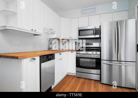 A small kitchen with stainless steel appliances, white cabinets, and a natural light colored wood counter top. - Stock Photo