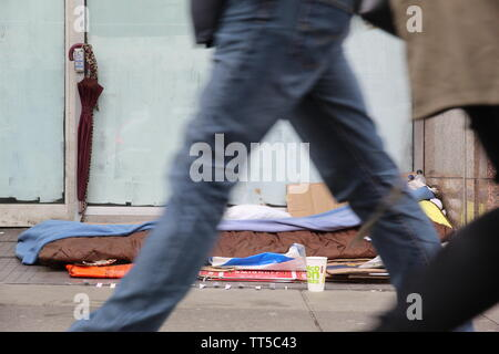 People walking past a homeless spot at the entrance of a closed down store - Stock Photo