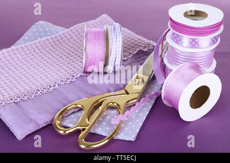 Ribbons with scissors and fabrics close up - Stock Photo