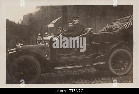 Vintage Edwardian Photographic Postcard of a British Chauffeur, Young School Boy and a Cat Riding in a Classic Motor Car. Taken in December 1909. - Stock Photo