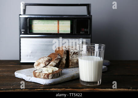 Rye bread and glass of milk on wooden cutting board on wooden table on radio set and light wall background - Stock Photo