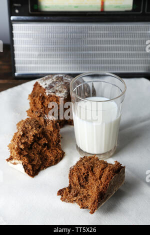 Rye bread and glass of milk on white fabric napkin on wooden table on radio set and light wall background - Stock Photo