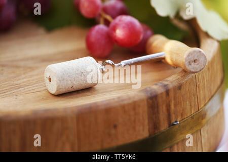 Corkscrew on wooden barrel close-up - Stock Photo
