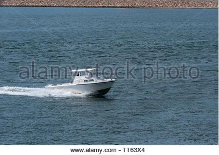 New Bedford, Massachusetts, USA - June 14, 2019: Small cabin cruiser heading into New Bedford - Stock Photo