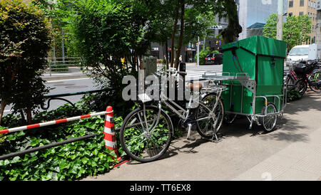 Tokyo, Japan - May 13, 2019: A delivery bicycle with a green cart attached behind it, parked at the roadside. Such bicycle courier is common in Japan.