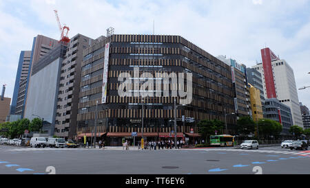 Tokyo, Japan - May 13, 2019: Cityscape of Tokyo. A unique buildings decorated with wooden planks on its outer wall in front of a cross road junction.