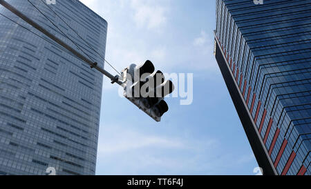 Tokyo, Japan - May 13, 2019: A traffic light with two high-rise buildings in the background. Looking at an upward angle.