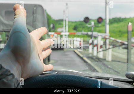 The hand of man inside the car. The car stopped in front of a closed barrier and a red traffic light before the railway crossing. - Stock Photo