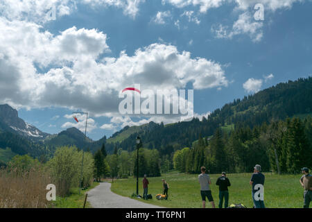 Schwarzsee, FR / Switzerland - 1 June 2019: instructors and students work together during a training course for paragliding in the Swiss Alps of Fribo - Stock Photo