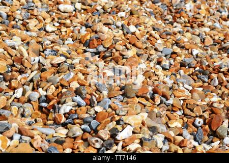 Pebble beach of big oval colorful stones brightly illuminated. - Stock Photo