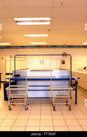 Two laundry carts sitting in front of a row of washers in a coin operated laundromat. - Stock Photo