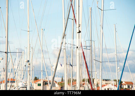 Masts of sailing boats fleet anchored in marina with town houses in the background - Stock Photo