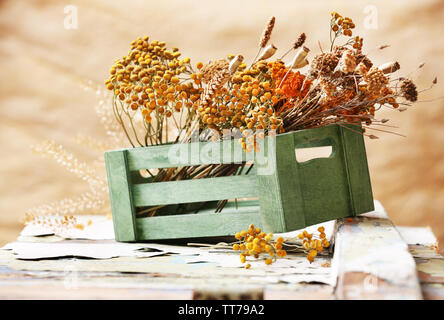 Dried flowers in crate on light background - Stock Photo