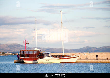 Vodice, Croatia - April 30, 2019: Sailing boats anchored by the pier in Adriaic sea - Stock Photo