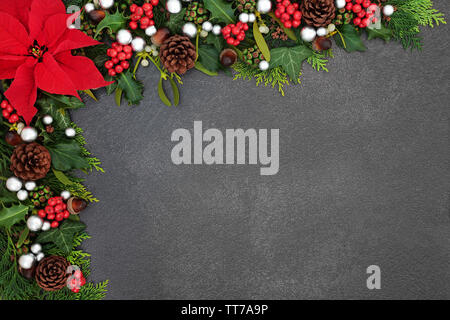 Poinsettia flower background border with silver ball baubles, holly, mistletoe and winter flora on grunge grey background with copy space. Traditional - Stock Photo
