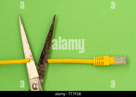 Steel scissors cut the yellow network cable connector.Internet censorship concept - Stock Photo