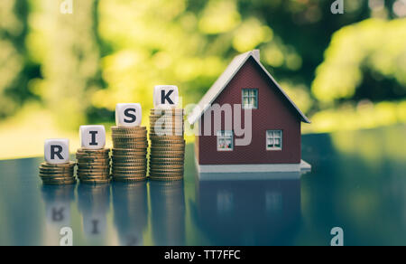 Concept of the financial risk to buy a house. Dice form the word 'risk' placed on increasing high stacks of coins next to a model house. - Stock Photo