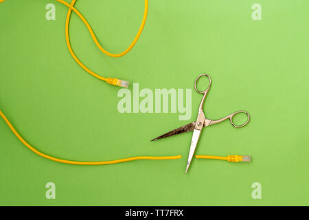 Scissors cut the yellow network cable connector. Internet censorship concept - Stock Photo