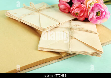 Old letters and book with flowers on wooden background - Stock Photo