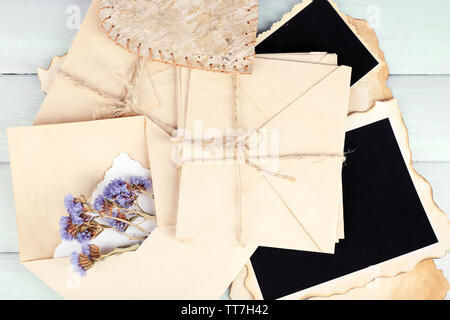 Old envelopes with photo papers and dry flowers on wooden background - Stock Photo