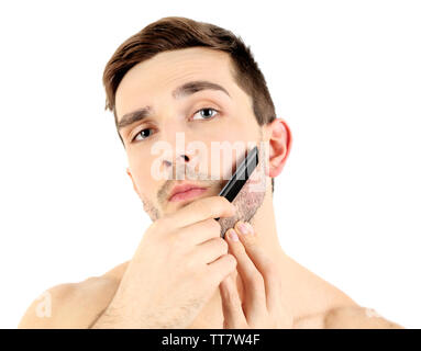 Handsome young man combing his beard isolated on white - Stock Photo