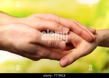 Male and female hands on bright background - Stock Photo